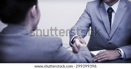 Young business partners sitting at a table shaking hands - stock photo