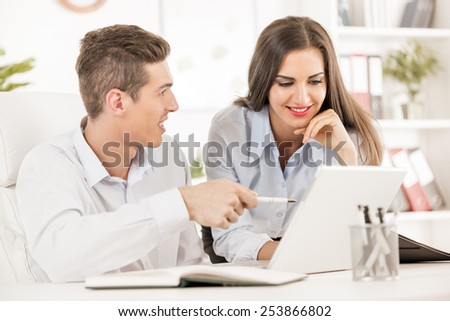 Young business people, businessman sitting at an office desk and showing something on a laptop, next to him is a businesswoman leaning against the table and looks at a laptop with a smile.