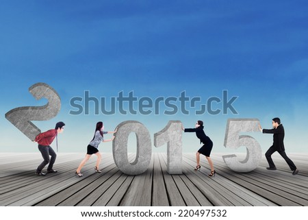 Young business people composing number 2015 under blue sky - stock photo