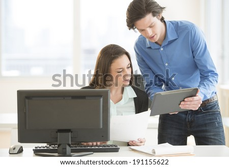 Young business people discussing over digital tablet at desk in office - stock photo