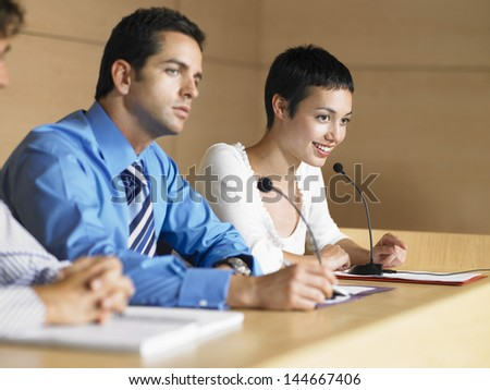 Young business people giving presentation in conference room