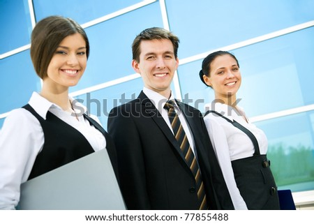 Young business people go along modern office building - stock photo