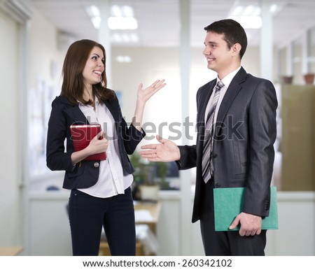 Young business people having discussion. Open space office background. - stock photo