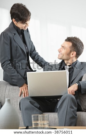 Young business people having meeting at office sitting on couch working on laptop computer.