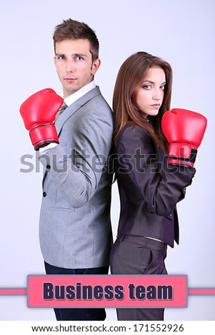 Young business people in boxing gloves on grey background - stock photo