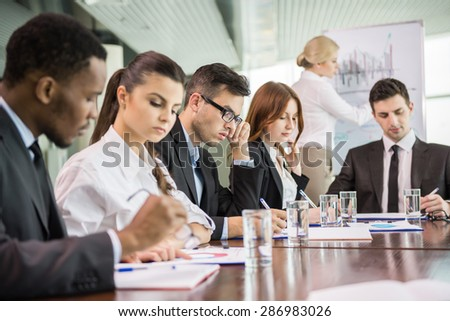 Young business people in suits sitting at meeting room and listening speaker. - stock photo