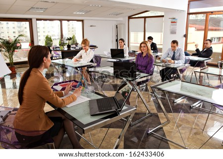 young business people meeting with their leader. modern office classroom with students listening to their trainer - stock photo