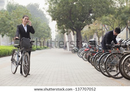 Young Business people parking their bikes and talking on the phone in Beijing - stock photo