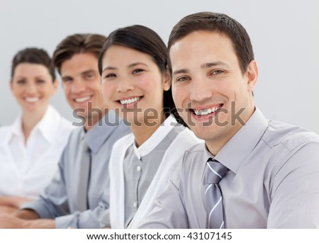 Young business people sitting in a line smiling at the camera