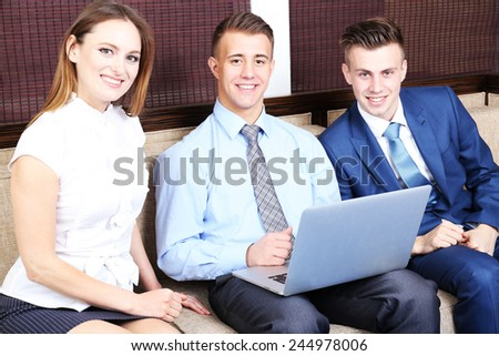 Young business people sitting on couch in office - stock photo