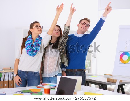 Young business people standing at office near desk and pointing up. - stock photo