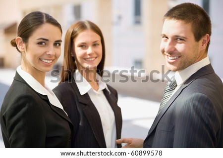 Young business people talk against a building of office - stock photo