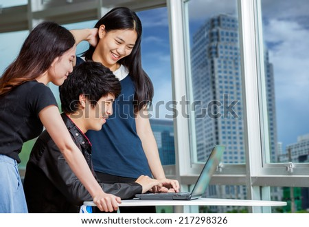 Young business people team sitting at desk, using computer at business training, smiling - stock photo