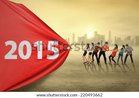 Young business people try to pull number 2015, symbolizing an effort for progress in 2015 - stock photo