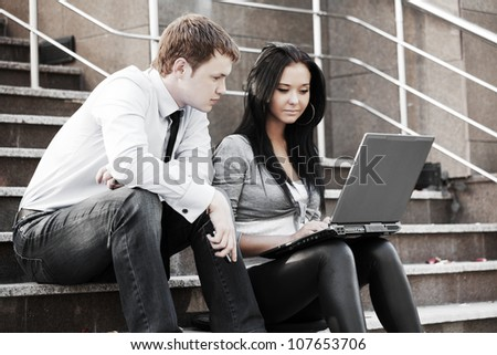 Young business people using laptop - stock photo