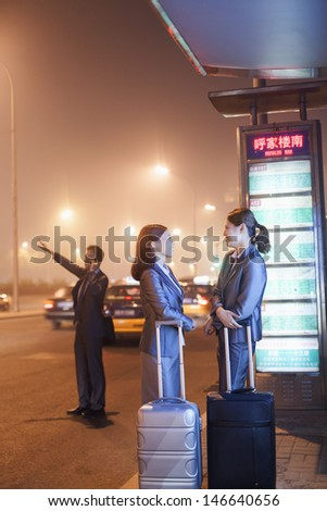 Young business people waiting for a taxi - stock photo