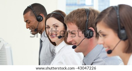 Young business people with headset on working in a call center - stock photo