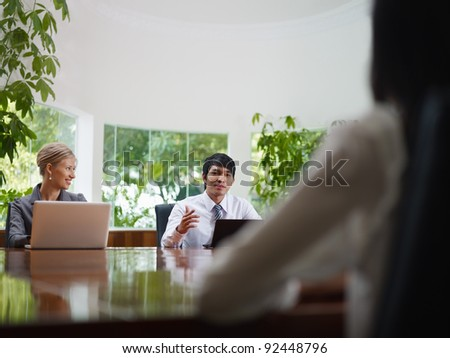 Young business people with laptop computers at meeting in conference room. Front view, copy space - stock photo