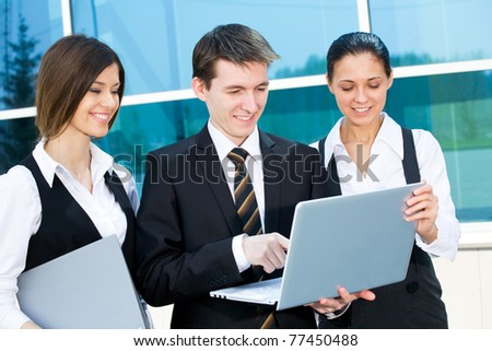 Young business people work on the laptop against a building of modern office