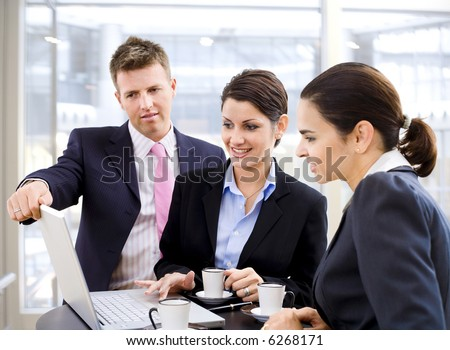Young business people working over a laptop computer and drinking coffee.