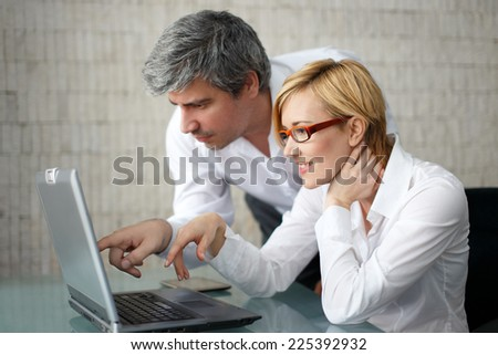 Young business people working over a laptop computer, businesswoman smile - stock photo