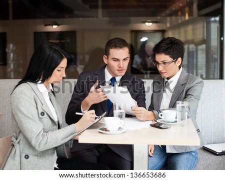 Young business people working over a paperwork and drinking coffee - stock photo