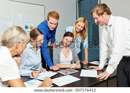 Young business people working together as a team in the office with tablet computer - stock photo