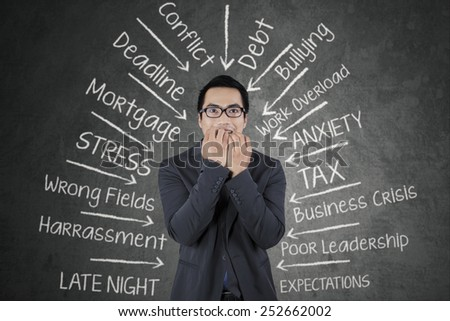 Young business person biting his nail with scared expression, facing many pressure - stock photo