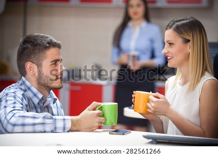 Young business person drinking coffee with a colleague in an office - stock photo