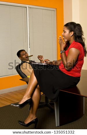 Young business professional flirting his secretary as she takes notes.