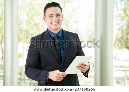 Young business student using a tablet computer and smiling - stock photo