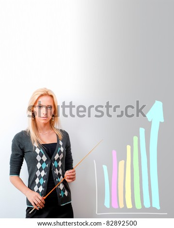 Young business teacher showing growing profit with graph on white board