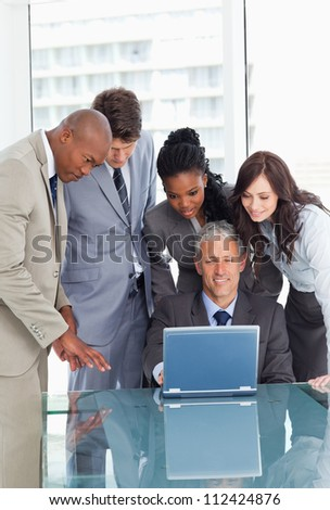 Young business team earnestly listening to their mature manager - stock photo
