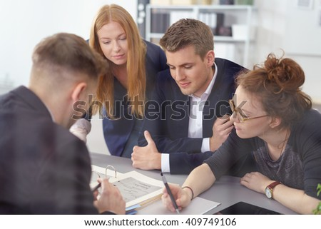Young business team having a brainstorming session sitting grouped around a binder taking notes of new ideas - stock photo