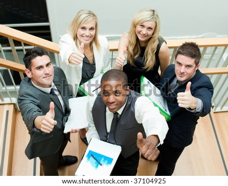 Young business team having a meeting on stairs with thumbs up - stock photo
