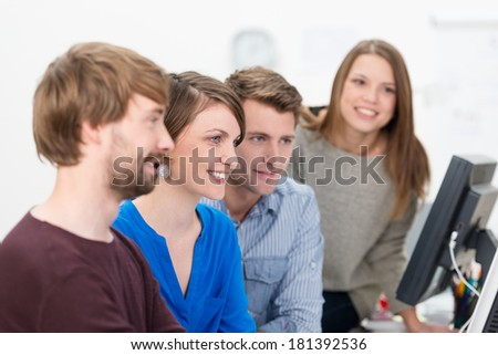 Young business team having a meeting sitting together at a desktop monitor brainstorming a problem