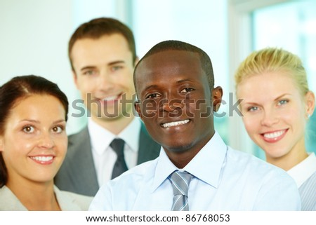 Young business team looking at camera and smiling - stock photo