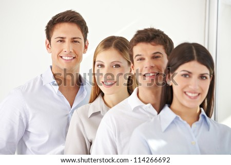 Young business team standing behind each other in a row - stock photo