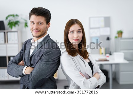 young business team with crossed arms looking at camera - stock photo