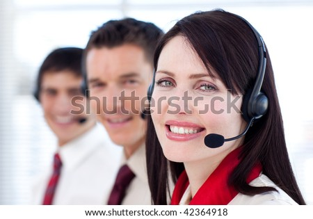 Young business team with headset on smiling at the camera - stock photo