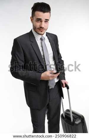 young business traveler with trolley suitcase making phone call - stock photo