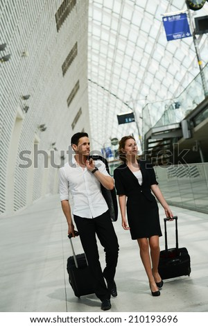 young business travelers commuters man and woman walking in a public station - stock photo