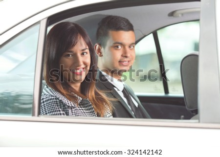 Young business woman and a man sitting on the back seat of the car and smiling to camera