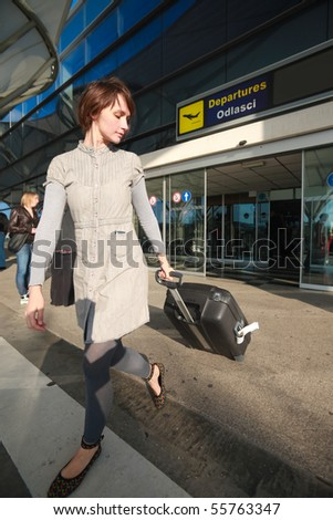 Young business woman at airport with luggage - stock photo