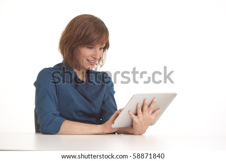 Young business woman at desk with touch pad computer - stock photo