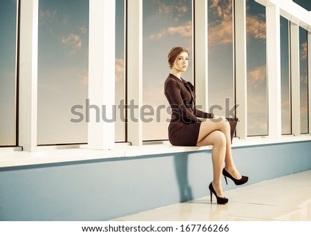 young business woman at office building windowsill