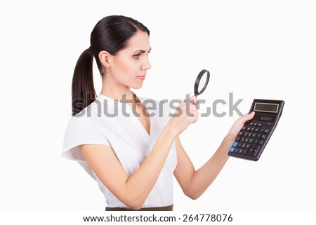 Young business woman calculating finance and looking in loupe isolated - stock photo