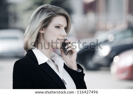 Young business woman calling on the phone against a car parking - stock photo