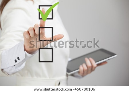 Young business woman checking on checklist box. Gray background. - stock photo