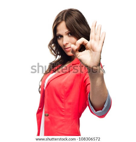 Young business woman doing Ok gesture. Focus on hand - stock photo